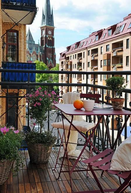 mala terasa sa rozim cvećem i sklopivim stolicama
